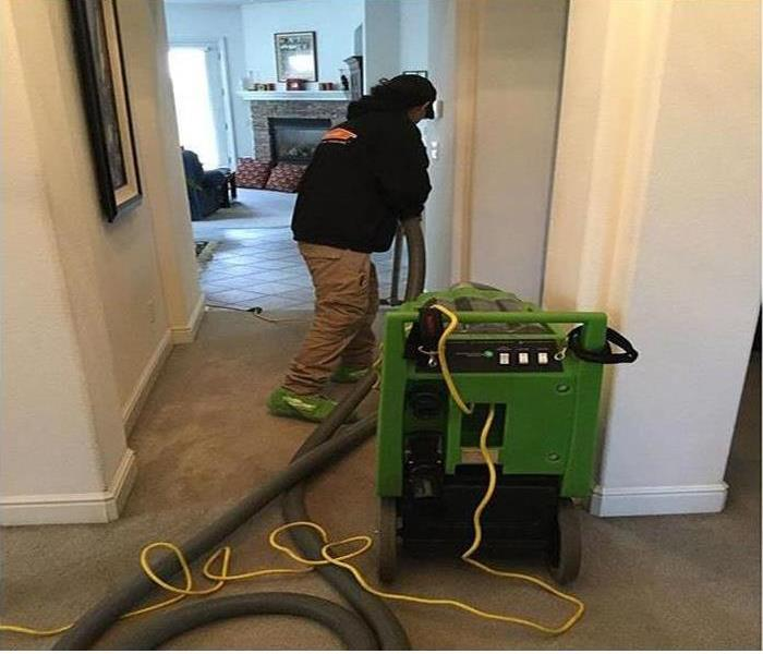 Our technician drying the carpets with our equipment in a home after water damage struck