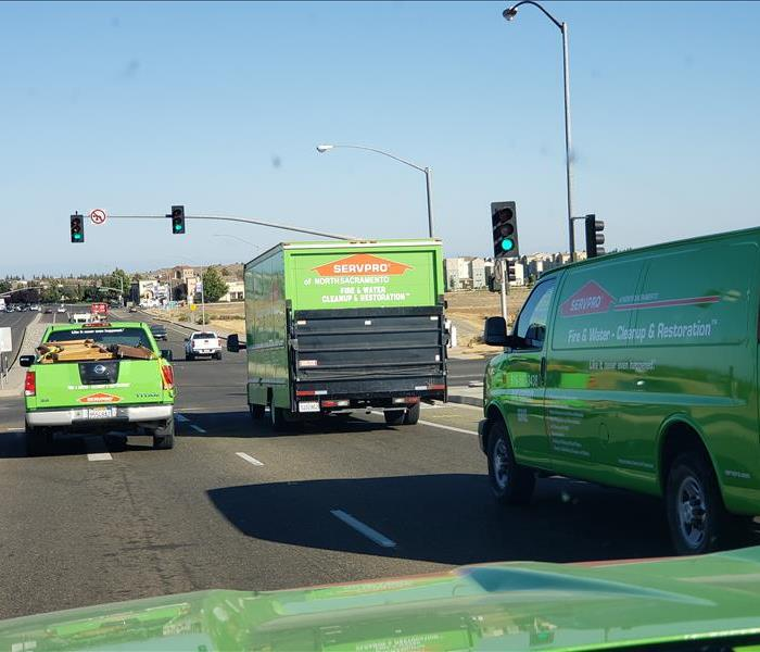 Four SERVPRO vehicles sitting at a red light.